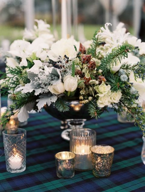 a frozen wedding centerpiece of white blooms, evergreens and pale foliage