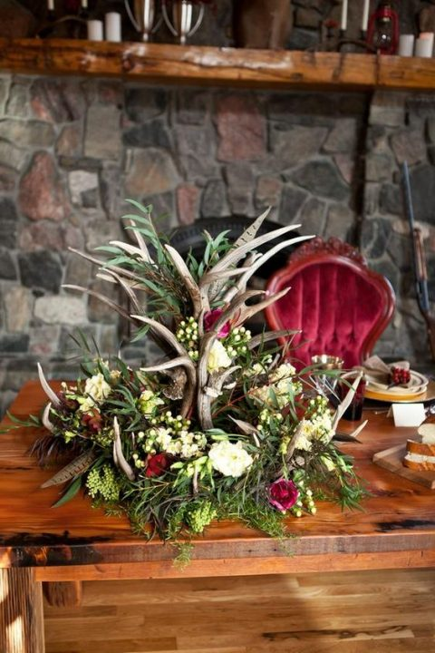 a gorgeous woodland-inspired centerpiece with antlers, different blooms, greenery and feathers