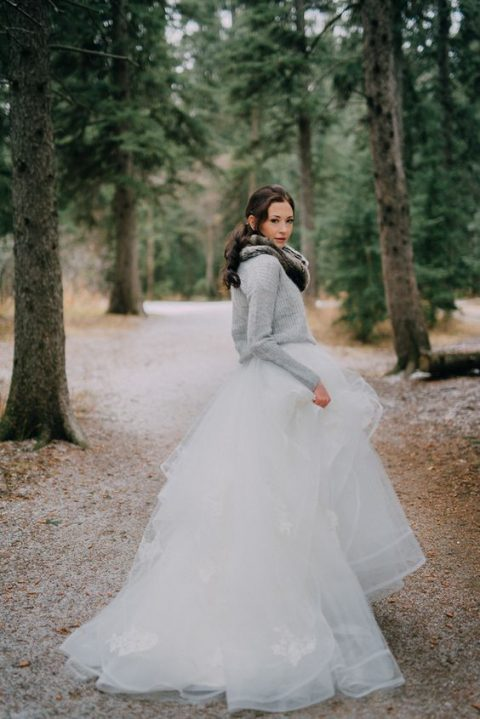 a grey comfy sweater over a princess-style wedding dress and a faux fur scarf