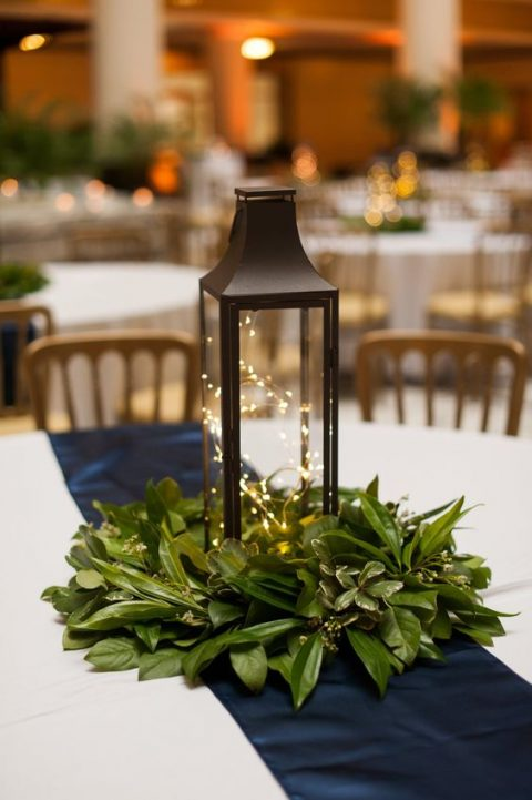 a holiday centerpiece of a lantern with LEDs and a fresh greenery wreath