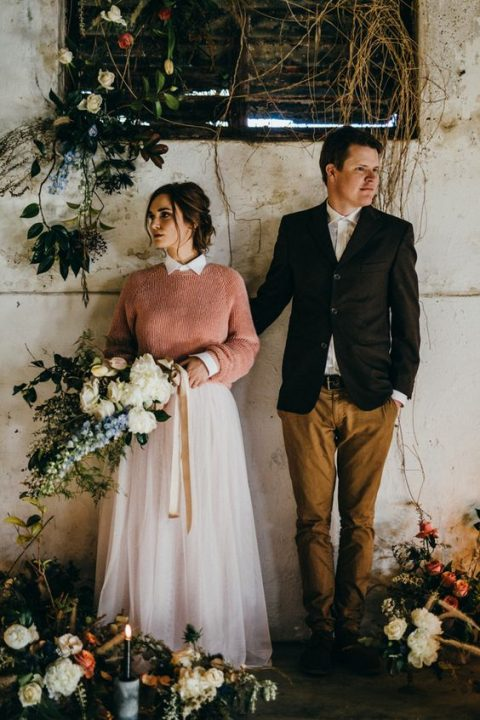 a peachy pink sweater over a pink high neckline wedding dress
