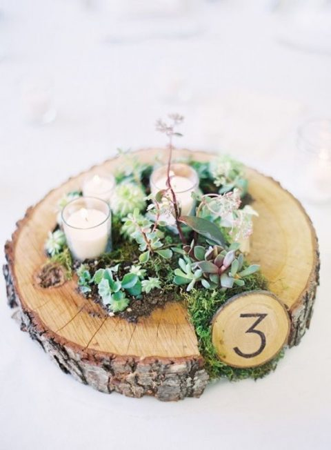 a rustic wedding centerpiece of a wood slice planter with succulents and moss, candles and a table number