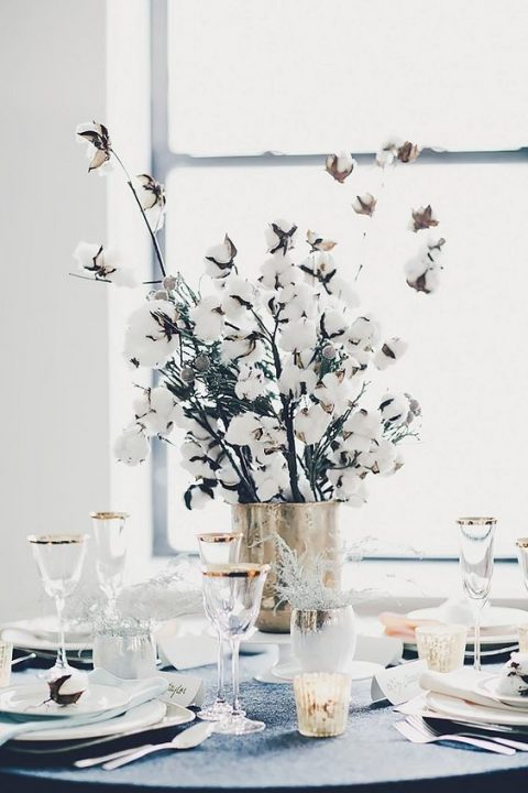 a simple and cozy winter wedding centerpiece of a gilded vase and cotton branches