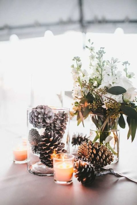 a simple winter wedding centerpiece with pinecones, candles and white blooms