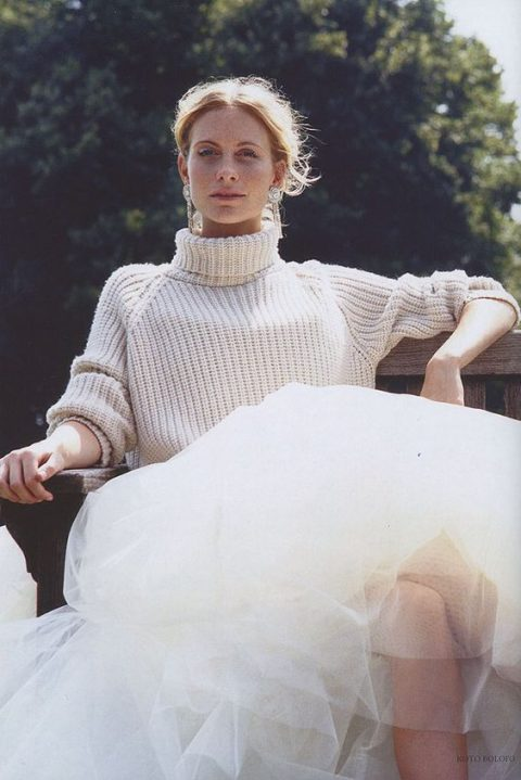 a slouchy chunky off-white turtleneck sweater over a princess-style wedding gown and statement earrings