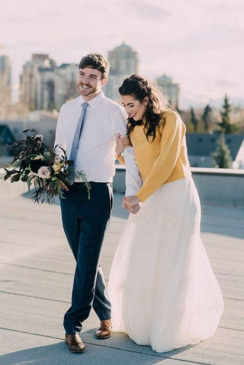 a sunny yellow sweater put on over a romantic lace wedding dress