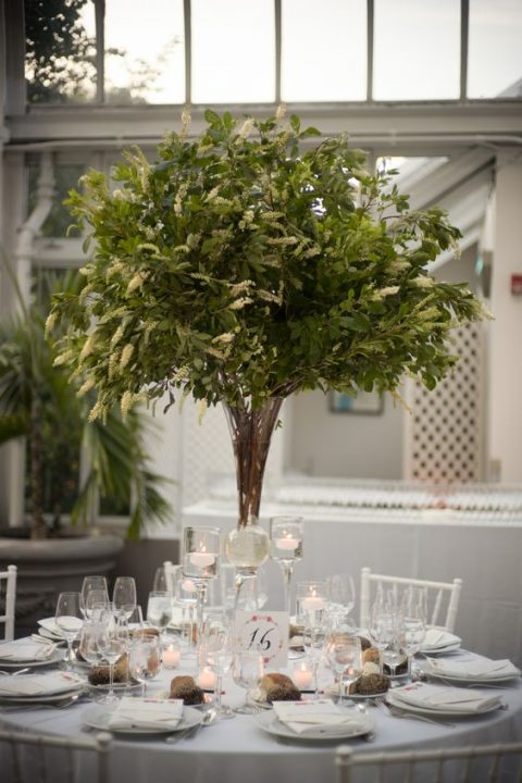 a tall non-floral centerpiece and pinecones on the table