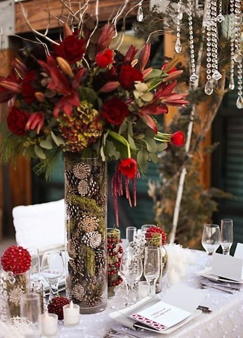a tall wedding centerpiece of a vase filled with pinecones and marsala-colored blooms