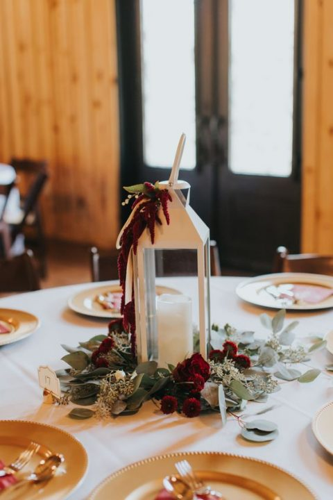 a winter wedding centerpiece of a white lantern with maroon blooms and greenery