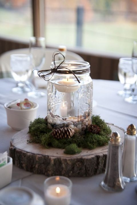 a wooden slice with a jar with a flowing candle, moss and pinecones for a rustic touch