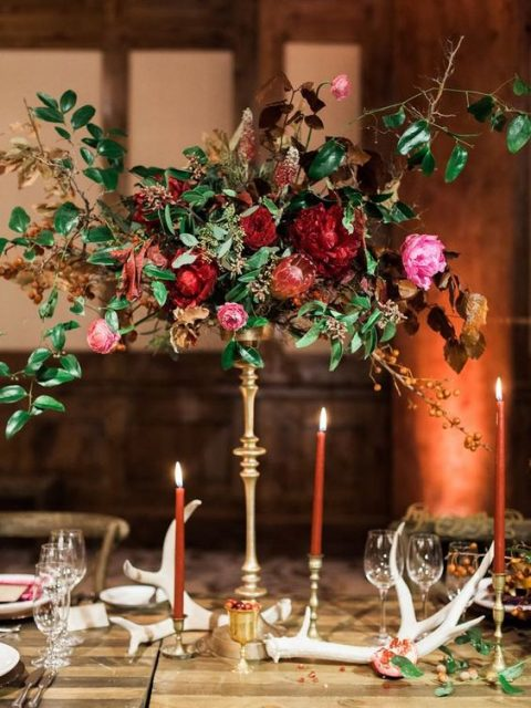 an elegant tall floral centerpiece with red and pink blooms, candles and greenery