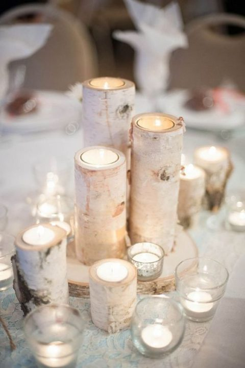 birch candle holders placed on a birch slice and surrounded with additional candles in glass