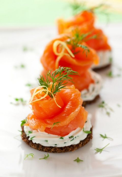 crackers, cream cheese and salmon with greenery on top