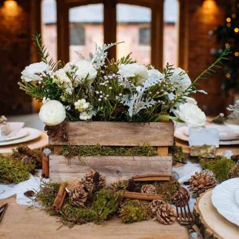 rustic crate with greenery and flowers placed on moss with pinecones and cinnamon bark