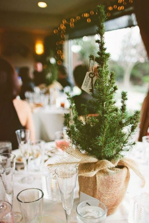 small pine trees in heavy burlap with vintage keys as simple rustic centerpieces