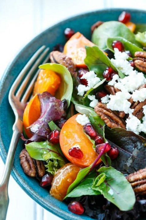winter salad with fruits, nuts, herbs and cheese with citrus vinaigrette