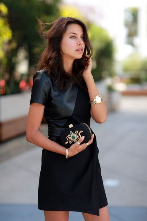 a black fabric and leather asymmetrical mini dress with short sleeves and a black clutch with gold snakes