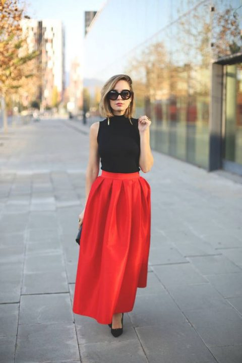 a black sleeveless top, a red pleated fullmaxi skirt, black heels and sparkly earrings