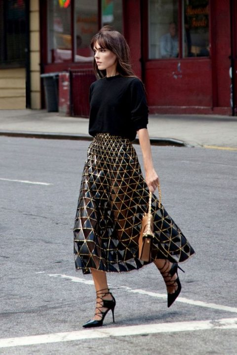 a black sweater, a gorgeous black geometric midi skirt with a shiny touch, lace up shoes and a small bag
