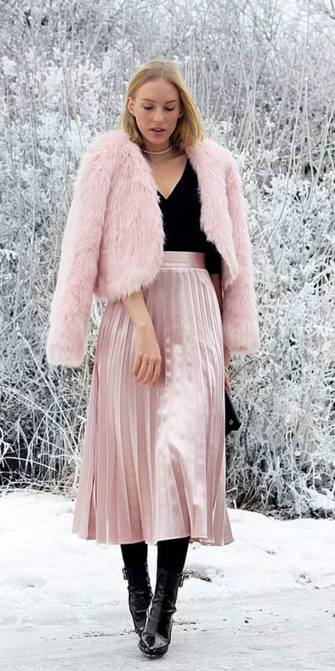 a black top, a pink velvet pleated midi, black heels, a faux fur coat and a black clutch