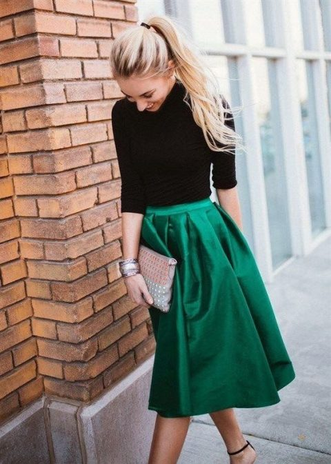 a black turtleneck, a pleated emerald midi skirt, heels and a metallic clutch