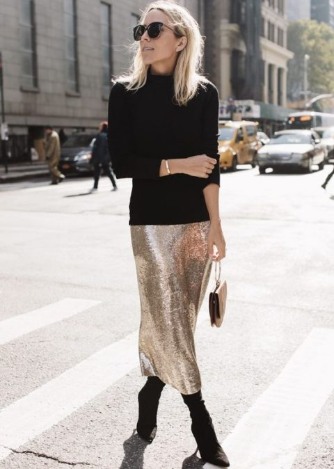 a black turtleneck, a silver sequin midi skirt, black boots and a trendy bag