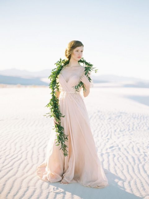 a blush spaghetti strap draped wedding gown with an A-line skirt