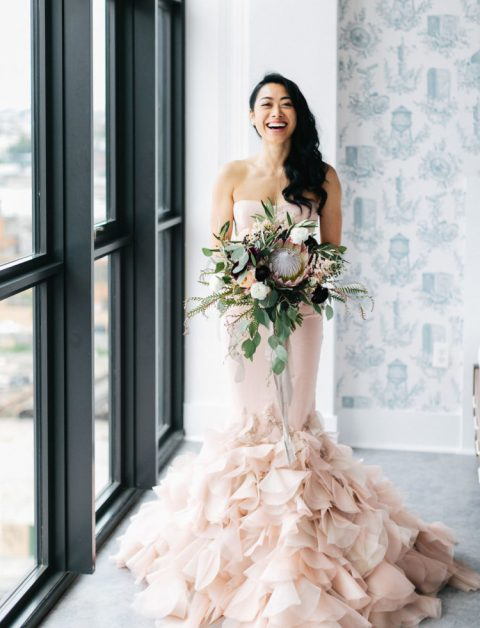 a blush strapless mermaid wedding dress with a ruffled tail