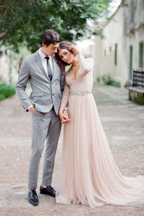 a blush wedding dress with a plunging neckline, long lace sleeves and an embellished sash