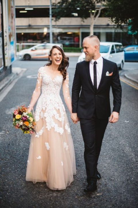 a blush wedding dress with an illusion neckline, sleeves and white floral appliques all over the dress