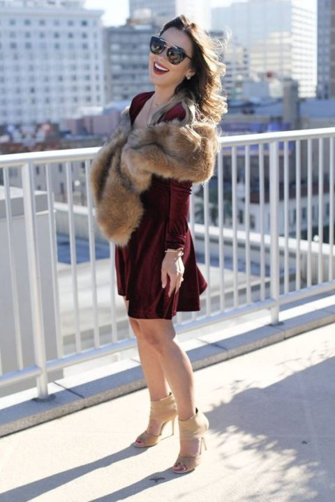 a burgundy velvet over the knee dress with long sleeves, a faux fur stole, nude heels