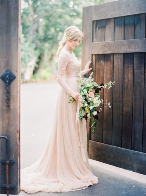 a cute blush wedding gown with a lace bodice and long sleeves and a draped skirt