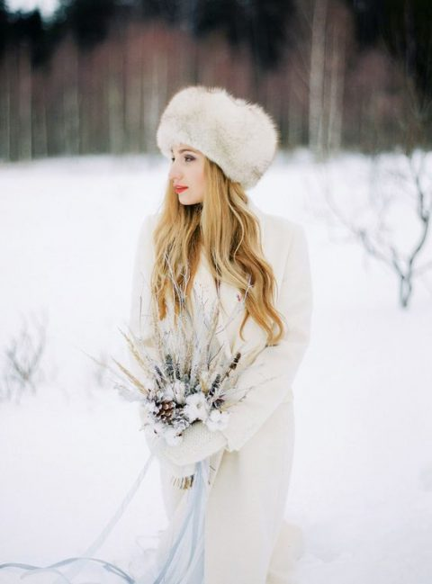 a dressed up bride in a coat, faux fur hat and mittens for a winter ceremony