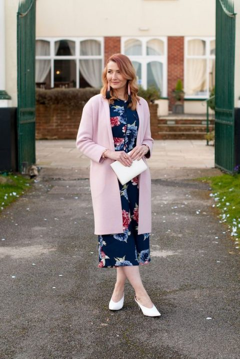 a navy floral midi dress, a pink cardigan, white heels, a matching clutch and tassel earrings