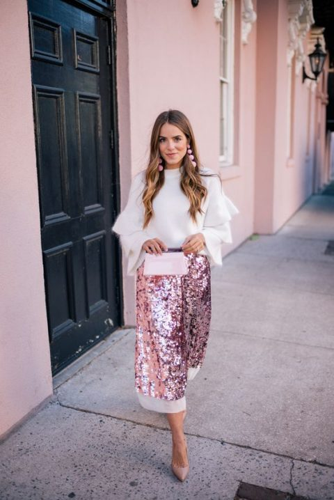a pink sequin midi skirt with a white edge, a white cahmere sweater with ruffled sleeves, pink earrings and nude heels