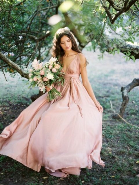 a pink silk wedding gown with thick straps and a plunging neckline for a romantic bride