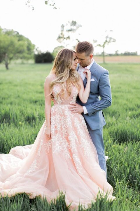 a pink sleeveless wedding dress with a plunging neckline and pearl floral embroidery all over the gown