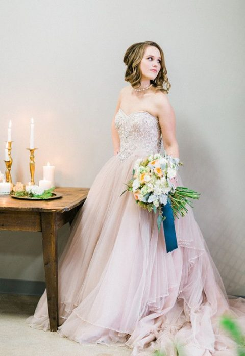 a pink strapless wedding dress with an embellished bodice and a layered skirt plus a train