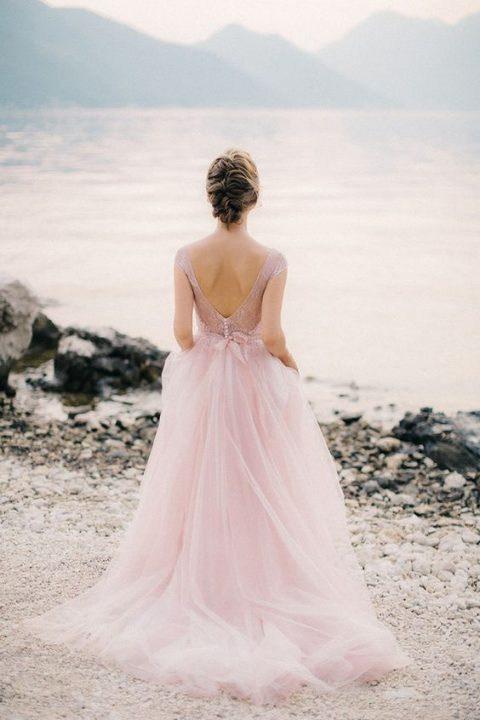 a pink wedding gown with a lace applique bodice, cap sleeves, an open back and a layered skirt