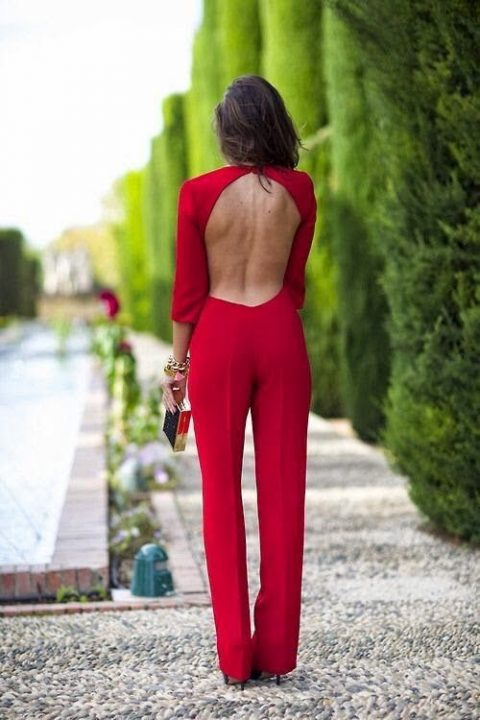 a red fitting jumpsuit with half sleeves and an open back plus a metallic clutch