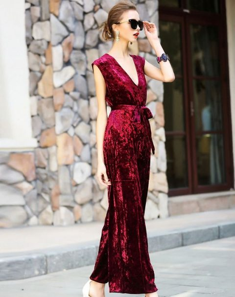 a red velvet belted jumpsuit with no sleeves and a sash plus statement earrings