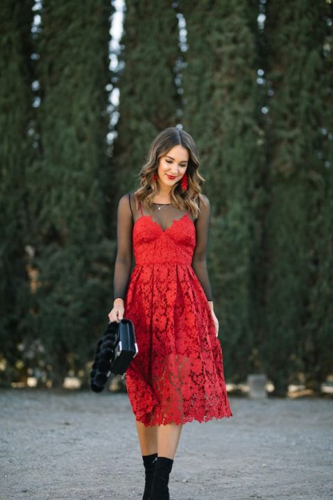 a sheer black top, a red lace dress over it, red statement earrings and sock books for a whimsy touch