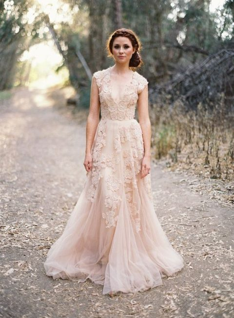 a sleeveless blush pink wedding dress with lace appliques and a deep V-neckline
