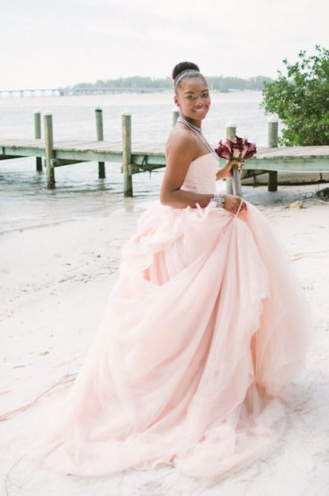a strapless pink off the shoulder princess-style wedding dress with a layered skirt