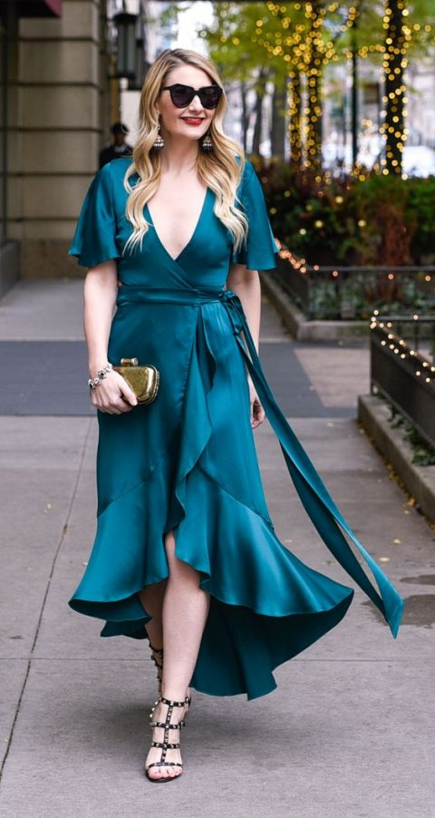 a teal high low midi dress with a deep V-neckline, a ruffled edge and a slit, spike shoes and a metallic clutch