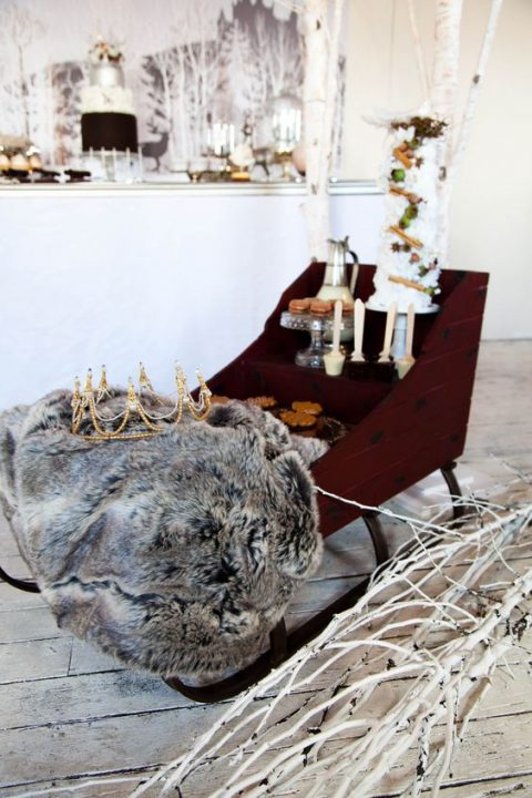 a wedding dessert table styled with a sledge and faux fur