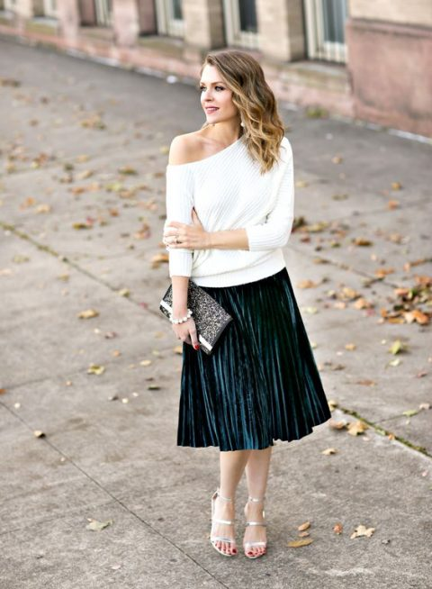 a white one shoulder sweater, a dark grene pleated midi skirt, silver strappy heels