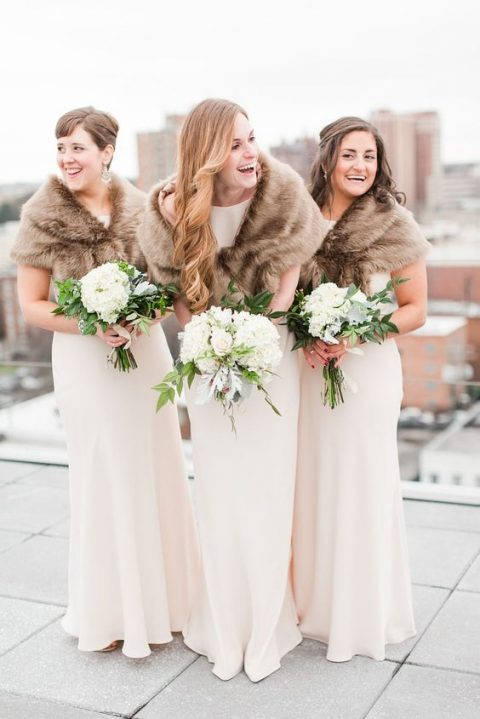 bridesmaids covered up with faux fur that contrasts the dresses