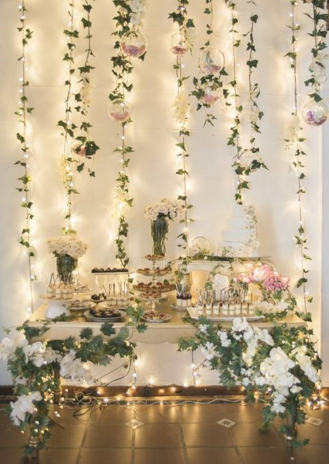 a beautiful dessert table with lush florals, greenery and glass bubbles with petals