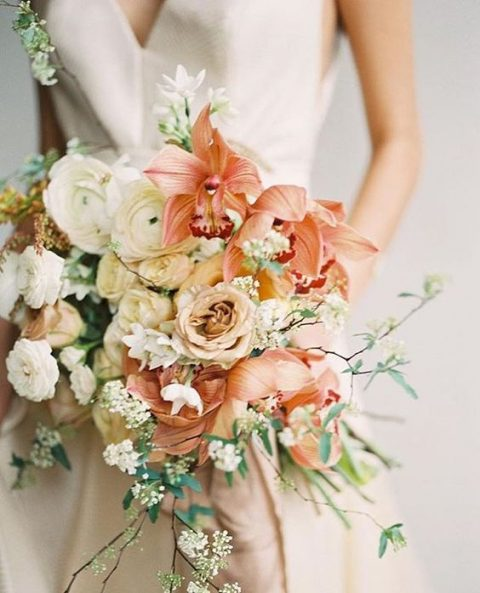 a beautiful wedding bouquet with white, neutral and coral blooms